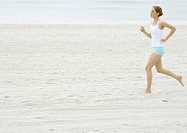 Young woman running on beach (thumbnail)