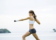 Young woman working out with weights, outdoors (thumbnail)
