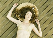Woman in bikini lying on deck, starfish in hair, eyes closed