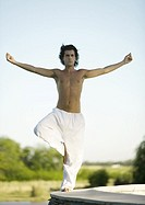 Man standing in tree pose outdoors