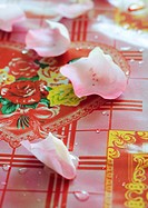 Rose petals on decorative tablecloth