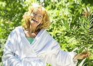 Senior woman in bathrobe holding branch of shrub, laughing