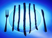 Asparagus on plate, knife and fork beside