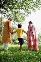 Grandparents With Grandson Walking in Park