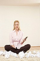Businesswoman sitting cross-legged on a rug and holding a mobile phone