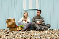 Mid adult couple sitting on pebbles with a basket of fruit