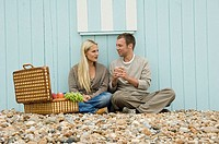 Young couple sitting on pebbles with a basket of fruit