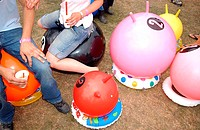 High angle view of a man and a woman sitting on space hoppers