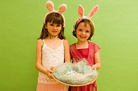 Portrait of two girls holding an easter basket filled with chocolate eggs