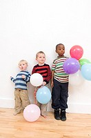 Three boys standing on a hardwood floor and holding balloons