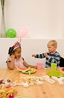 Boy gesturing at a girl in a birthday party