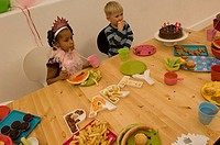 High angle view of two children sitting at a birthday party
