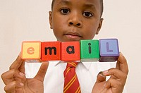 Portrait of a boy holding alphabet blocks spelling the word email