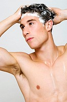 Man with shampoo in wet hair and muscular torso