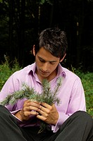 Close-up of a young man holding a plant