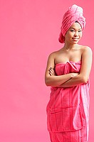 Woman wrapped in a pink towel, wearing pink turban, arms crossed