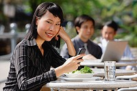 Businesswoman using mobile phone at outdoor cafe, text messaging, smiling at camera