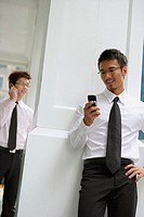 Businessman looking at mobile phone, hand on hip, people in the background