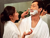 Couple in bathroom, woman applying shaving cream to man´s face