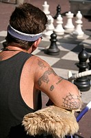 Man with tatoos on arm watching chess, Max Euweplein, Amsterdam, Holland, Netherlands