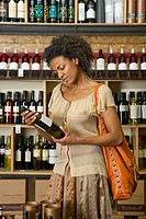 Woman examining wine bottle