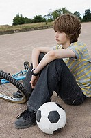 Teenager with bike and football