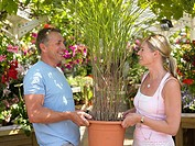 Couple carrying a plant in garden centre