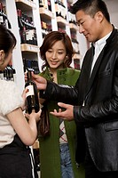 Employee helping couple select wine