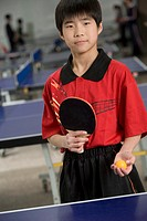 Young ping-pong player holding ball
