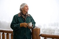 Senior woman standing by a railing and holding a coffee cup