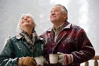 Senior couple holding coffee cups and looking up