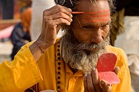 Mangal giri, a sadhu applying a Shiva tika on his forehead after his Holy bath