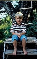 A boy sitting on the wooden steps