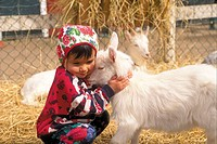 A child hugging goat