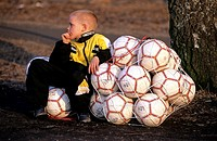 A boy sitting near the footballs