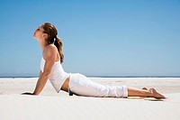 Woman exercising yoga on beach