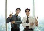 Two businessmen making victory sign, smiling at camera