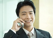 Businessman using cell phone, smiling at camera, portrait