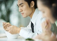 Businessman eating with chopsticks, looking away
