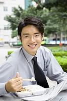 Young businessman eating takeout food outdoors