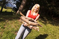 Young woman holding firewood