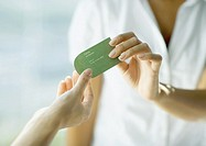 Woman handing second woman business card, close-up of hands