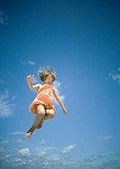 Girl jumping, sky in background, low angle view