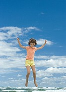 Girl jumping, sky and ocean in background, full length