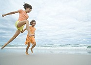 Two girls running and jumping on beach