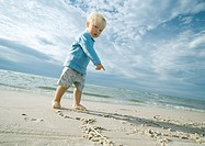 Toddler standing on beach, looking at camera and pointing at sand