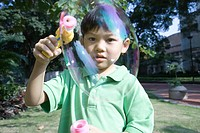 Boy making bubbles with bubble wand
