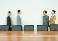 Business executives standing, facing associates arriving in conference room