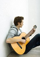 Young man sitting on floor, playing guitar