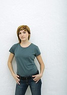 Young woman standing with hands in pockets, portrait